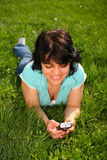 Woman lying on the lawn using mobile. Smiling brunette woman in T-shirt lying on the lawn using mobile Royalty Free Stock Image