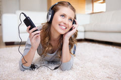 Woman lying in the living room enjoying music Royalty Free Stock Photos
