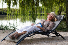 Woman lying in lounge chair Stock Photos