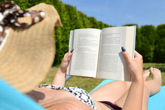 Woman lying on lounger in garden and reading a book. Stock Photos
