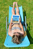 Woman lying on lounger in garden. Stock Photo