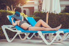 Woman lying on a lounger by the pool Royalty Free Stock Photography