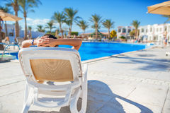 Woman lying on a lounger by the pool at the hotel Stock Image