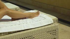 A woman is lying on a lounger on a terrace, moving her legs, sunbathing and tanning. Tanned legs close up stock video