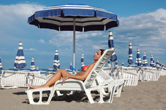 Woman lying on lounger under beach umbrella Royalty Free Stock Photo