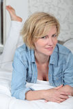Woman lying on a made bed Royalty Free Stock Photography
