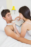 Woman lying on man and reading novel on bed Stock Photography