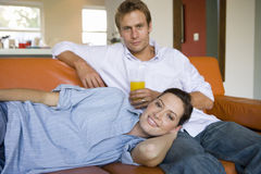 Woman lying on man's lap on sofa, smiling, portrait Royalty Free Stock Photography