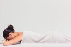Woman lying on massage lounger Stock Photos