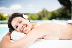 Woman lying on massage table with salt scrub on back Royalty Free Stock Images