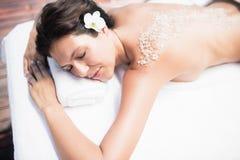 Woman lying on massage table with salt scrub on back Stock Image