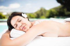 Woman lying on massage table with salt scrub on back Royalty Free Stock Photo