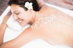 Woman lying on massage table with salt scrub on back Stock Photos