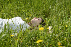 Woman lying on meadow Stock Images