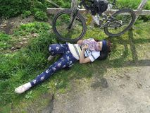 Woman is lying near the bike Royalty Free Stock Image
