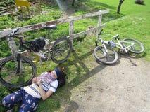 Woman is lying near the bike Stock Photos