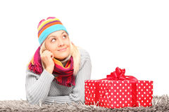 Woman lying next to a Christmas present Royalty Free Stock Photos