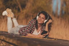 Free Woman Lying On Lake Docks Listening To The Music Stock Photo - 189592260
