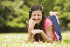 Woman lying outdoors with flowers smiling. At camera Stock Photography