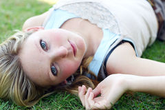 Woman lying outside. Young woman lying down on grass Stock Image