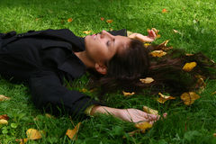 Woman lying in park. A beautiful young woman in autumn park stock image