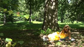 Woman lying on plaid and reading books in park on beautiful sunny summer day. 4K stock video