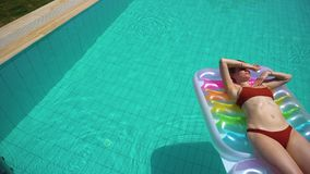 Woman lying on pool float. Female in brown swimwear lying on inflatable float and sunbathing in pool with clean water stock video footage