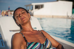 Woman lying by the pool sunbathing Stock Photography