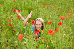 Woman lying in a poppy field Stock Photos