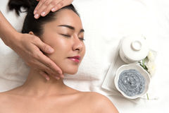 Woman lying and preparation face or head massage in spa. Close up of beautiful young asian women lying with closed eyes and preparation face or head massage in royalty free stock images