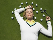 Woman Lying On Putting Green With Golf Balls. Beautiful female golfer lying on putting green with golf balls and club Royalty Free Stock Photo