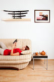 Woman lying and reading a book. Woman is lying on a sofa at home and reading a book. Image on the wall was photographed by me royalty free stock images
