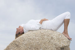 Woman lying relaxed on top of rock outdoor Royalty Free Stock Photography