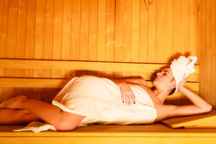 Woman lying relaxed in wooden sauna Royalty Free Stock Image