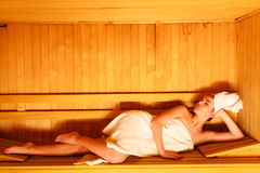 Woman lying relaxed in wooden sauna Stock Photos