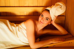 Woman lying relaxed in wooden sauna Stock Image