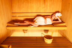 Woman lying relaxed in wooden sauna Royalty Free Stock Photo