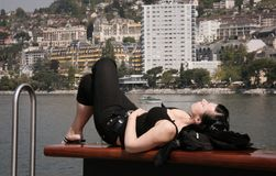 Woman. Lying and relaxing on bench at quay in Montreux, Switzerland on a sunny day Stock Image