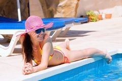 Woman lying and relaxing by a large swimming pool Royalty Free Stock Image
