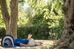 Woman lying relaxing in the shade of a tree in a  garden Stock Photos