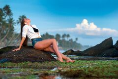 Woman Lying on Rock Against Sky Stock Photography