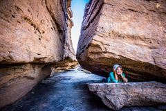 Woman Lying Between Rock Formation at Daytime stock photos
