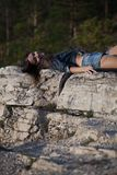 Woman lying upon rocks Royalty Free Stock Photos