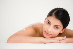 Woman lying with salt scrub on the back Royalty Free Stock Image