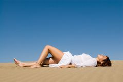 Woman lying in the sand. Relaxing royalty free stock photography