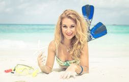 Woman lying on the sand holding starfish and wearing fins. Stock Image