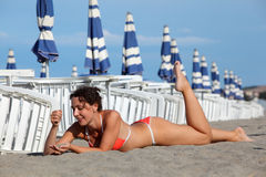 Woman lying on sand and sunbathe on beach. Beautiful young woman lying on sand and sunbathe on beach. in background rows of white loungers and blue umbrellas Stock Images