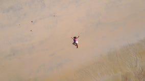 Woman lying on sand Stock Photos