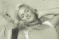 Woman lying on sandy beach relaxing during summer Royalty Free Stock Photos