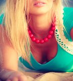 Woman lying on sandy beach relaxing during summer. Portrait of attractive blonde woman lying on sandy beach relaxing during summertime Stock Images